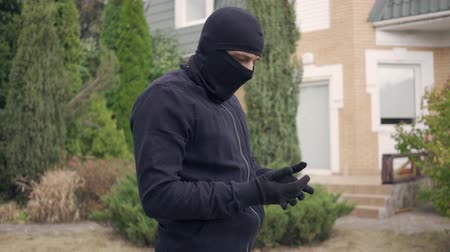 přestupek : Thief in black clothes and balaclava before breaking into house. The guy going to steal things in rich house. Concept of offense against the law, robbery, burglary Dostupné videozáznamy
