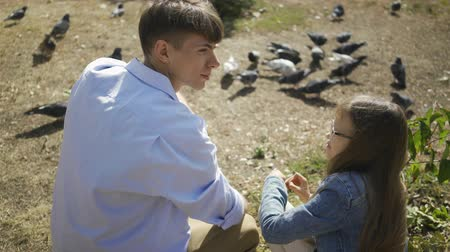 feed back : Elder brother with his small sister having fun and happily talking in park feeding pigeons on weekend or family day