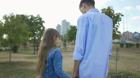 сестры : Backs of elder teenage brother taking hand of his little sister and happily talking in park on the background of city