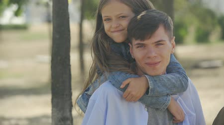 perdão : Portrait of cute little girl happily embracing with love and care her elder teenage brother in park at sunny autumn day