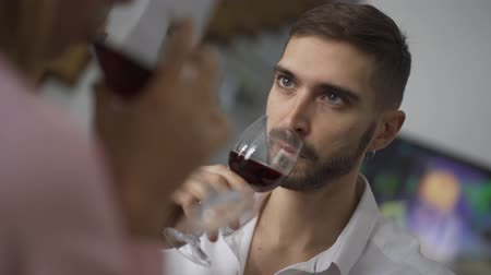 kırmızı şarap : Beautiful young caucasian man and his wife drinking red wine sitting at home. Shooting over the shoulder. Happy married couple has romantic dinner at home. Man and woman clink glasses. Leisure indoors