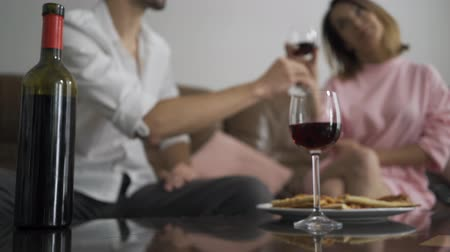 kırmızı şarap : Young caucasian man and his wife drinking red wine sitting at home. Married couple has romantic dinner at home. Man and woman clink glasses. Leisure indoors
