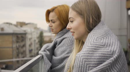 tratsch : Two caucasian girlfriends covered in blankets standing on the balcony looking away. Two women talking, chatting, gossiping. Meeting of female friends