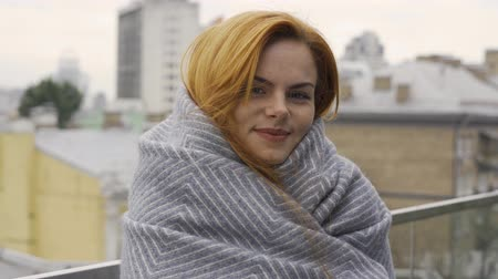 redhair : Portrait of caucasian woman with red hair covered in blanket. The girl looking at the camera standing on the balcony. Autumn leisure. Resting outdoors Stock Footage