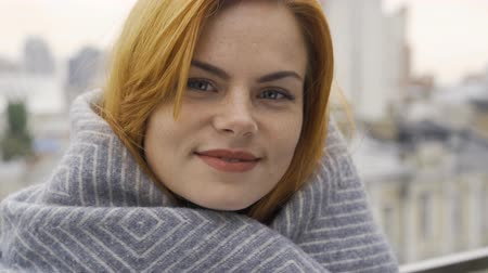 redhair : Close-up portrait of caucasian woman with red hair covered in blanket. The girl looking at the camera standing on the balcony. Autumn leisure. Resting outdoors Stock Footage