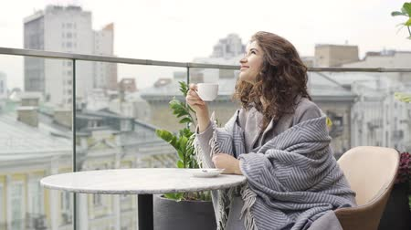 checked pattern : Young attractive caucasian woman covered in blanket drinking tea or coffee sitting at the table on the terrace. The girl looking away enjoying her beverage sitting on the balcony. Autumn leisure outdoors Stock Footage