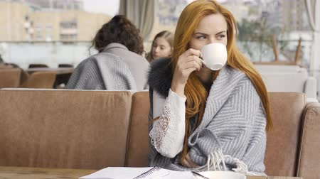 checked pattern : Young caucasian woman covered in blanket drinking tea or coffee sitting at the table on the terrace. The girl enjoying her beverage sitting on the caffee. Autumn leisure outdoors