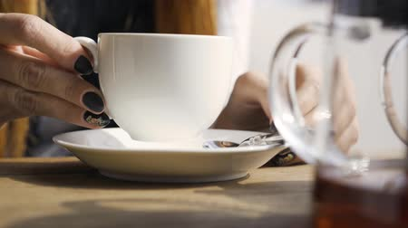 tırnak : Close-up hand of caucasian woman with black nails touching white tea cup while sitting in the cafe. Young woman relaxing indoors. Autumn leisure