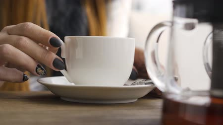 aromatik : Close-up hand of caucasian woman with black nails touching white tea cup while sitting in the cafe. Young woman relaxing indoors. Autumn leisure