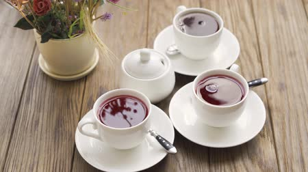 aromatik : Close-up of three cups of tea and bowl with sugar on the table in the modern cafe. Relaxing indoors. Hot tea for the three people