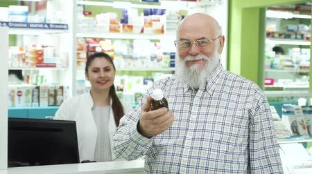 apotheker : Middle-aged bearded man in glasses looking at medication in the pharmacy and smiling to the camera. Pharmacist waiting for the customer to read the label. Healthcare and traditional treatment
