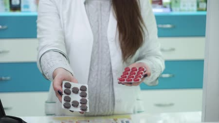 gyógyszerész : Young female pharmacist showing two variants of medications to the camera. Choice between black and red pills for the treatment. Healthcare and traditional medicine