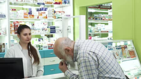 med : Middle-aged bearded man with runny nose coming to the pharmacy. Young female pharmacist offering the customer medication for the common cold. Buyer examining unknown remedy Stock Footage
