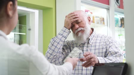 med : Elderly bearded man with headache coming to the pharmacy. Young female pharmacist offering the customer pills for the common cold. Buyer looking at the unknown medication and refusing to buy it