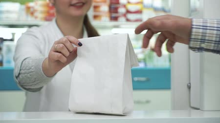 fogyókúra : Smiling pharmacist giving the white paper bag with medications to the male customer. Purchase process in the pharmacy. Healthcare and traditional medicine concept