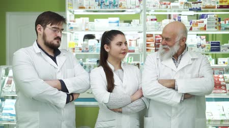 aimed : Three caucasian pharmacists looking at each other and at the camera. Highly professional employees staying at their workplace. People in white robes aimed at rescuing lives