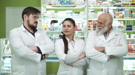 aimed : Three caucasian pharmacists of different ages looking at each other and smiling to the camera. Highly professional employees staying at their workplace. People in white robes aimed at rescuing lives