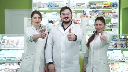 aimed : Three young caucasian pharmacists showing thumbs up to the camera and smiling. Highly professional employees staying at their workplace. People in white robes aimed at rescuing lives
