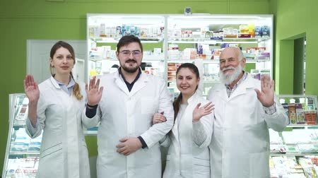 aimed : Four caucasian pharmacists of different ages waving to the camera and smiling. Highly professional employees staying at their workplace. People in white robes aimed at rescuing lives