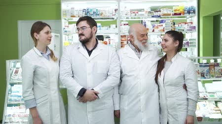 aimed : Four caucasian pharmacists looking at each other and smiling. Highly professional employees staying at their workplace. Confident workers in white robes aimed at rescuing lives Stock Footage