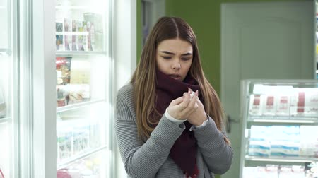 med : Young attractive girl with long dark hair trying nasal spray in the pharmacy. Caucasian woman buying efficient medication for the treatment of her runny nose. Satisfied customer of the drugstore