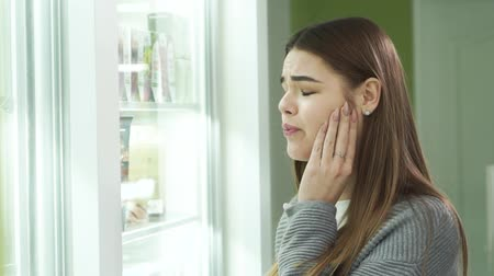 med : Young caucasian brunette with toothache staying at the pharmacy and choosing the pain medication. Beautiful woman selecting traditional medicine for the treatment. Healthcare concept Stock Footage