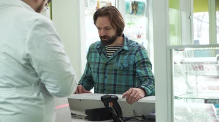 med : Adult caucasian man with beard dressed in shirt waiting for the pharmacist to pack his medications. Pharmacy worker serving his customer. Process of purchase in the drugstore Stock Footage