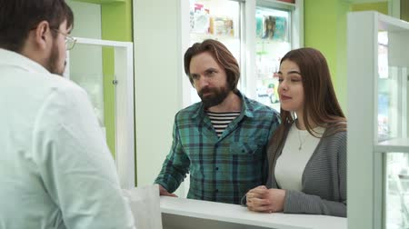 gyógyszerész : Young caucasian couple coming to the pharmacy to take their on-line order. Comfortable buying process in the drugstore. Satisfied smiling customers purchasing medications via online shopping