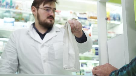 gyógyszerész : Young bearded pharmacist giving the white package with medications to the customer. Professional worker in white robe and glasses selling efficient drugs to the client. Healthcare concept