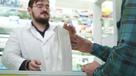 med : Young bearded pharmacist giving the white package with medications to the customer. Professional worker in white robe and glasses selling efficient drugs to the client. Healthcare concept