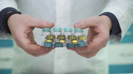 prescribe : White male hands showing colorful pills to the camera. Man in white robe offering choice between different types of medications. Pharmacy worker at his workplace Stock Footage