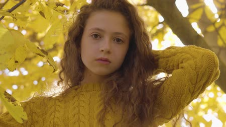 mustár : Cute redhead caucasian girl in mustard sweater standing in the autumn park in sunrays. Child with long hair and brown eyes looking at the camera on the background of yellow leaves