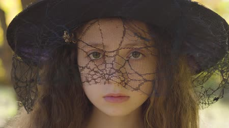 vychovávat : Close-up of a redhead caucasian girl in Halloween witch hat standing in the autumn park. Child with curly hair and brown eyes looking seriously at the camera