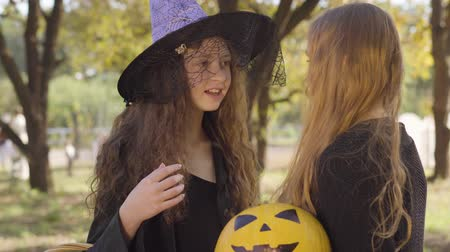 czarodziej : Cute caucasian redhead girl dressed in witch costume talking to her blonde friend. Two little friends discussing the celebration of All Saints Night