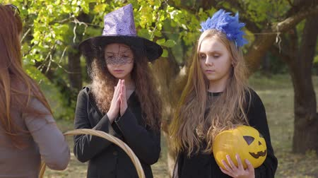 čarodějnice : Two caucasian children in Halloween costumes approaching to the redhead woman with straw basket on the foreground. Redhead girl rubbing hands and her blonde friend holding yellow pumpkin in hands Dostupné videozáznamy