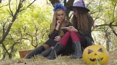 narożnik : Portrait of two caucasian girls in Halloween costumes sitting in the autumn forest and using tablet. Yellow pumpkin laying in the right bottom corner Wideo