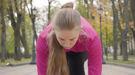 velocista : Close-up of confident young Caucasian girl at start position looking up and starting running. Attractive female runner training in the morning in the autumn park. Camera zooms in