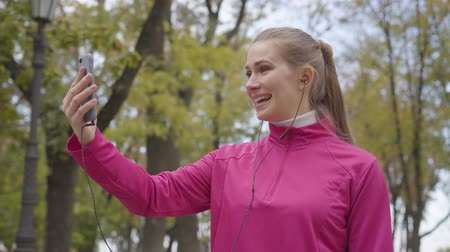 polegar : Portrait of smiling Caucasian sportswoman in pink sportswear talking through videochat and showing thumb up. Cheerful girl training in the morning outdoors. Sports concept
