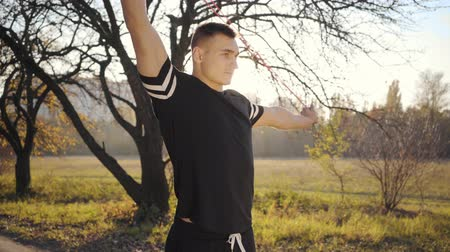 перемычка : Jump rope workout of a handsome Caucasian boy in the autumn park on sunset. Young man in sportwear training outdoors. Healthy lifestyle, sport concept