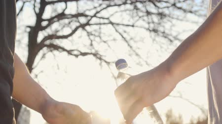 helping : Close-up of male Caucasian hands sharing water on sunset in the autumn park. Two adult boys shaking hands in sunlight. Healthy lifestyle concept