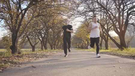 competitivo : Two sportive Caucasian boys running in the autumn park. Adult sportsmen stopping because of pain in heart. Healthy lifestyle concept