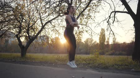 ugró : Jump rope workout of a young Caucasian girl in the autumn park on sunset. Woman in black sportwear training outdoors. Healthy lifestyle, sport concept