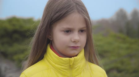 Close-up face of a pretty Caucasian girl with brown eyes listening to her mother or sister and shaking head. Cute child dressed in yellow coat standing in the autumn park