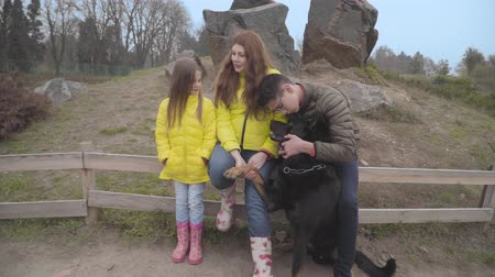 аналогичный : Teenage Caucasian boy in eyeglasses playing with black doberman as his mother and sister in similar yellow coats talking. Family spending weekends in autumn park. Children resting with pet outdoors
