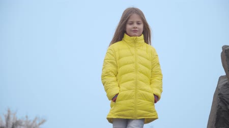 Portrait of a beautiful Caucasian girl in yellow coat on the background of blue sky. Cute little child looking away and smiling standing in the autumn park. Wind blowing her long hair Stock Footage