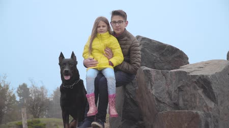 Teenage Caucasian brother in eyeglasses holding his younger sister on hands. Siblings looking at camera and smiling. Big black doberman sitting next to them. Family spending time with pet