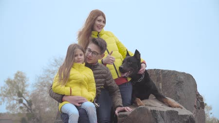 Happy Caucasian family sitting on rocks with their adorable dog. Elder brother and younger sister together with mother resting outdoors with big black doberman. Adult woman showing thumb up