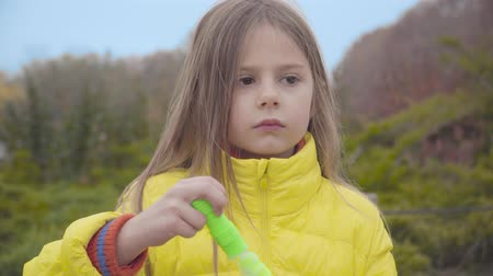 Cute Caucasian girl with long hair and brown eyes blowing soap bubbles outdoors. Pretty child resting in the autumn park on weekends Stock Footage