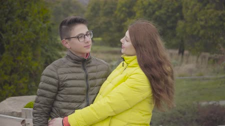 Young redhead Caucasian mother posing with her teenage son in the autumn park. Boy in eyeglasses and pregnant woman in yellow coat looking at each other, at camera, and smiling. Happy family outdoors