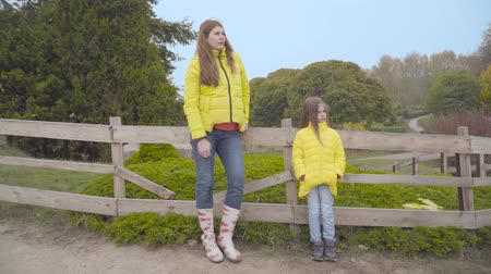 Mother and daughter in similar yellow coats and jeans standing next to the fence in autumn park and looking away. Caucasian family in casual clothes spending time together outdoors Stock Footage